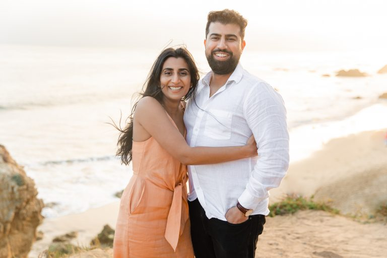 Newly engaged couple smile as the girl wraps her arm around the guy during their engagement shoot at El Matador Beach, photographed by Kyla Jeanette